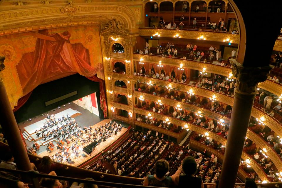 Ejemplo de Etiqueta ALT Accesible : En el Auditorio Nacional de música de Madrid lleno de gente, con vistas desde del ala izquierda en el balcón más alto. Mientras La Filarmónica de Madrid se prepara en el escenario para empezar la Novena Sinfonía de Beethoven, el escenario está lleno de músicos esperando las órdenes del director de orquesta.