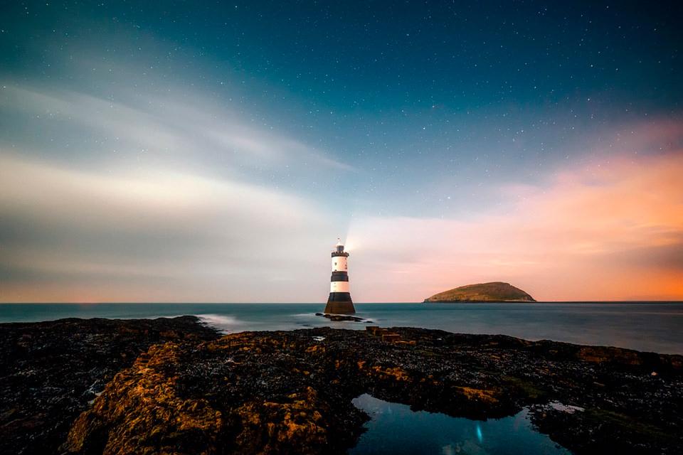 Ejemplo de Etiqueta ALT Accesible: Al anochecer en la playa mirando al faro encendido de Cabo Ortegal en Galicia bajo un cielo estrellado y las islas de Ons al fondo. El agua del mar es sedosa y en una charca cercana se refleja el brillo de una estrella.